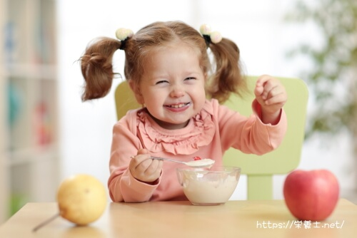 給食をおいしそうに食べる子ども