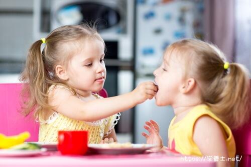 食事中の双子の女子